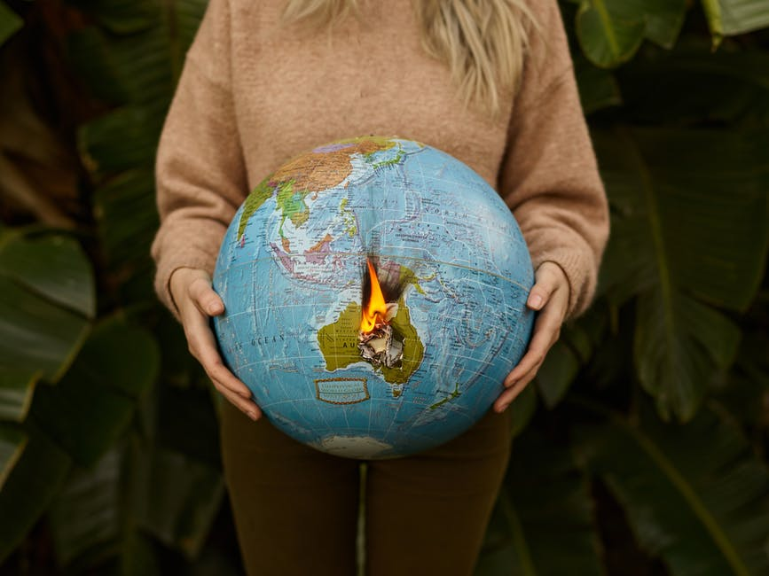 Crop woman with burning globe in hands