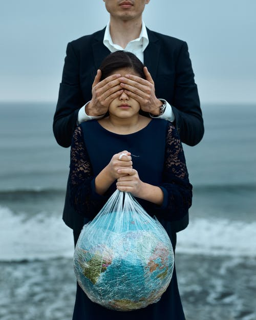 Man and girl with globe in hands and covered eyes