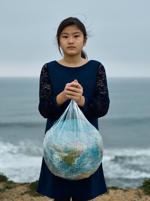 Unemotional Asian girl in black dress with Earth planet globe in plastic bag standing against blurred cloudy seashore environmental pollution problems concept