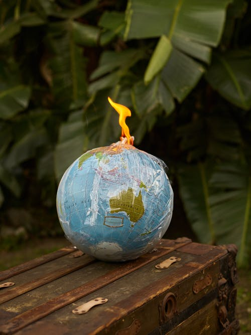 Environment ecology pollution concept burning Earth globe covered in transparent plastic bag in shape of bomb placed on wooden bench near green plants