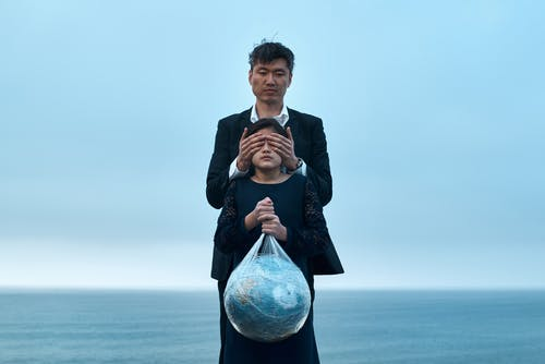 Asian male in formal wear standing near seashore and covering eyes of girl in black dress with Earth globe in plastic bag environment pollution concept
