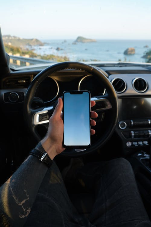 Crop anonymous driver using smartphone during road trip