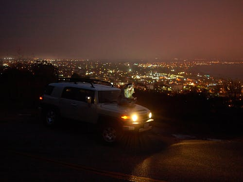 Young pensive woman sitting on hood of car and messaging on smartphone against cityscape at night