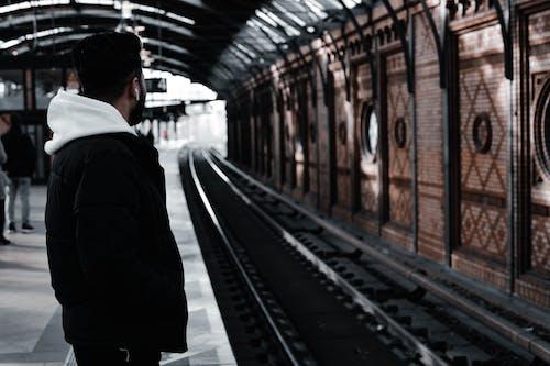 Man in Black Jacket Standing Beside Train Station