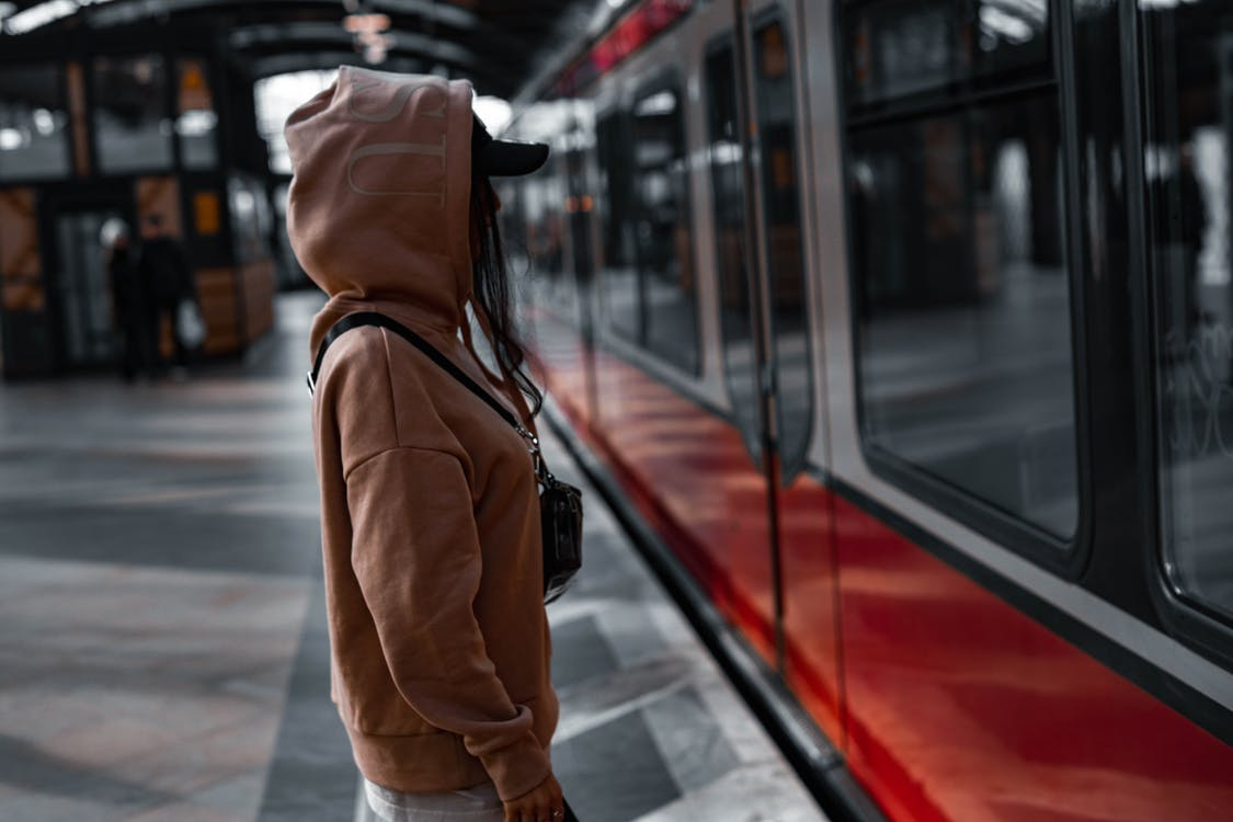 Person in Brown Jacket and Black Cap Standing in Front of Train