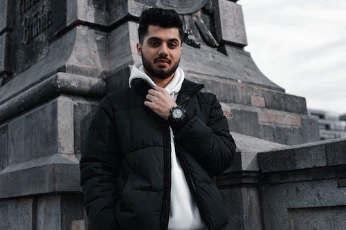 Man in Black Jacket Standing Near Gray Concrete Wall