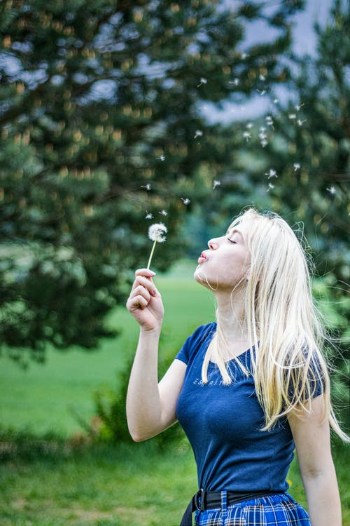 Side view of young female wearing casual clothes blowing dandelion while standing against green grass and trees