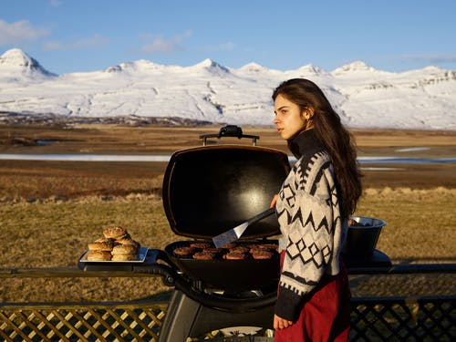 Young woman grilling meat during winter holidays