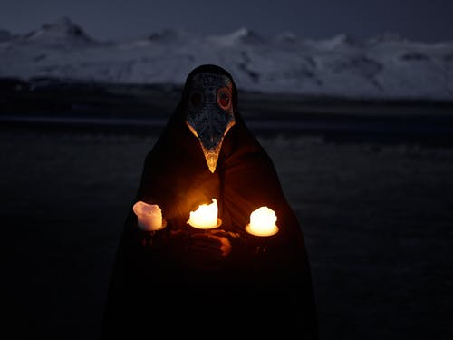 Unrecognizable person in plague mask standing in front of snowy hills at night and holding burning candles while looking at camera