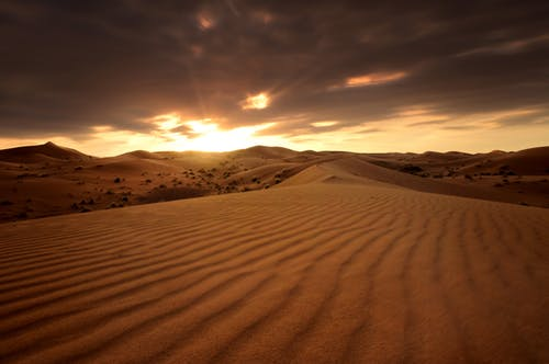 Brown Sand Under Cloudy Sky