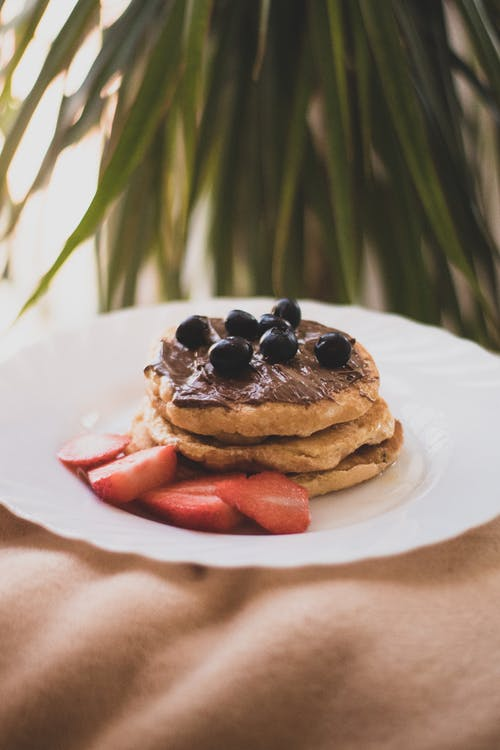 Pancakes With Blueberries and Strawberries on White Ceramic Plate