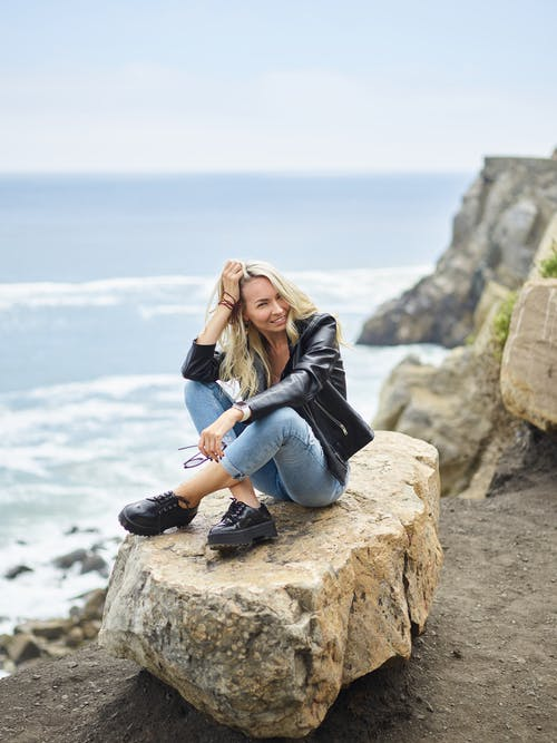Young smiling woman resting on rock above ocean coast
