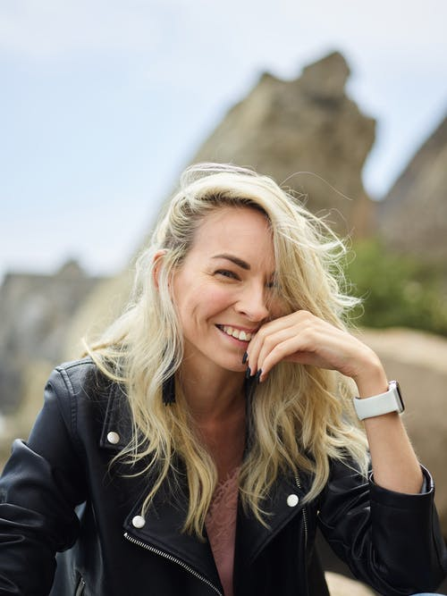 From below of young positive lady with blond hair in leather jacket smiling and touching face while looking at camera on sunny day