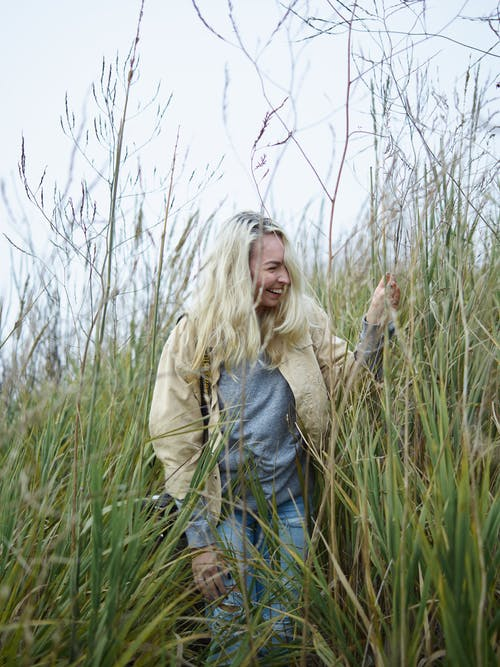 Young female traveler laughing in meadow