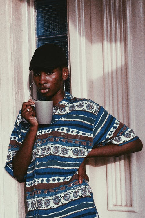 Young ethnic man with big earrings standing against white wall with mug of hot drink