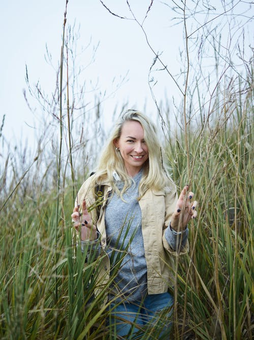Optimistic young woman smiling and touching dry reeds in field