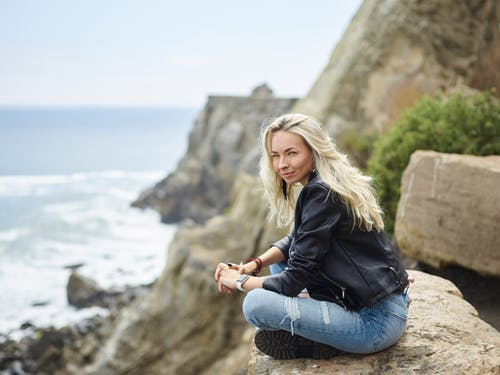 Confident young woman resting on stone against rocky seashore