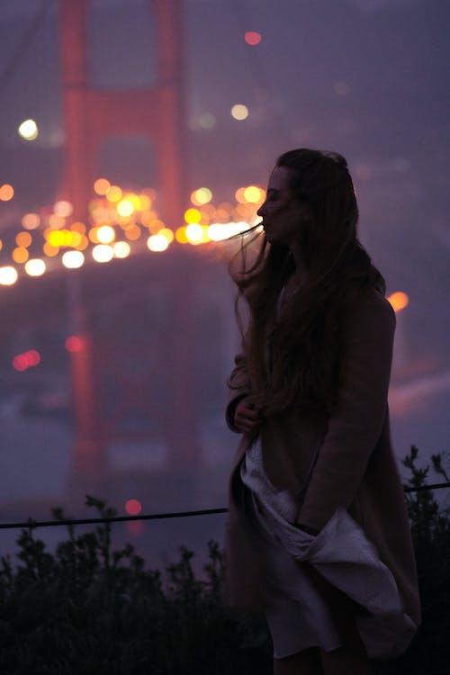 Melancholic young woman against illuminated city at night