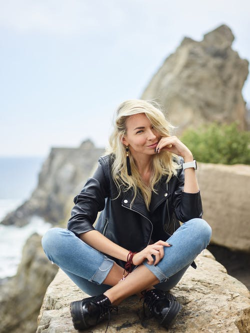 Full body of trendy positive young female in jeans and leather jacket sitting on stone with crossed legs and looking at camera against rocky ocean