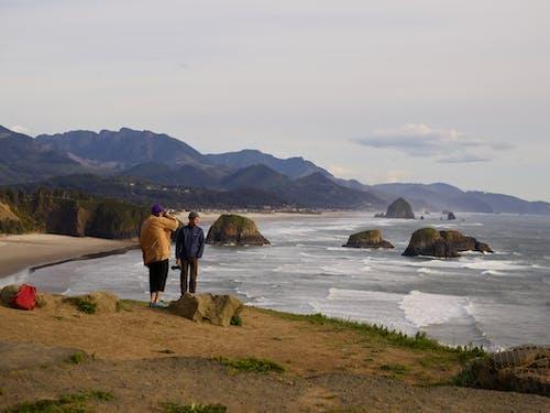 Anonymous travelers enjoying seascape during sundown