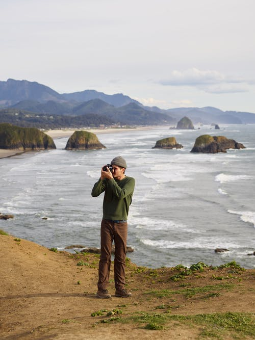 High angle of young male photographer in casual clothes standing on rocky viewpoint and taking pictures of amazing landscape with camera