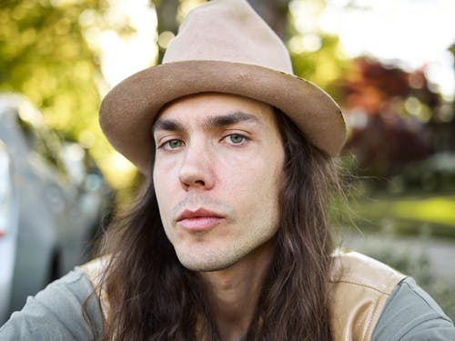 Portrait of young long haired man in hat