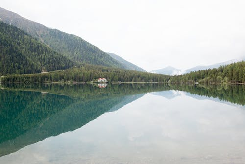 Photograph of Calm Body of Water and Mountain Ranges
