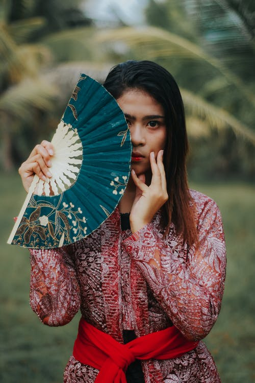 Woman in Red and White Floral Long Sleeve Shirt Holding Blue and White Hand Fan