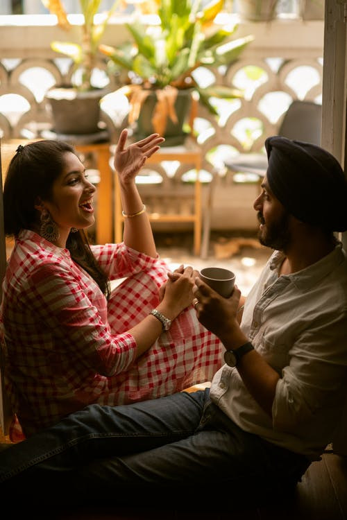 Young positive Indian couple discussing daily life and gesticulating