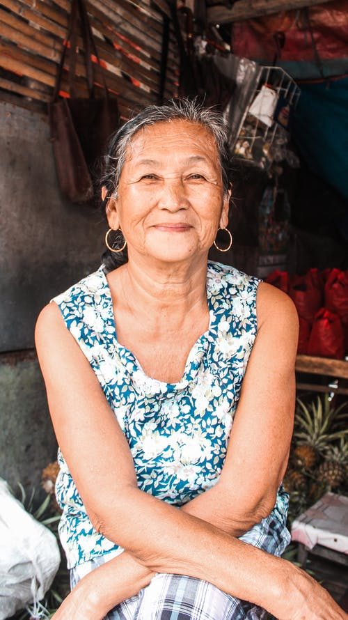 Cheerful ethnic aged female with earrings smiling brightly and looking at camera while sitting in hut