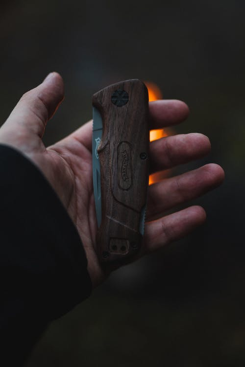 Person Holding Brown Wooden Folding Knife