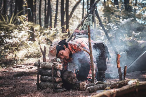 Ethnic man preparing bonfire in forest during expedition