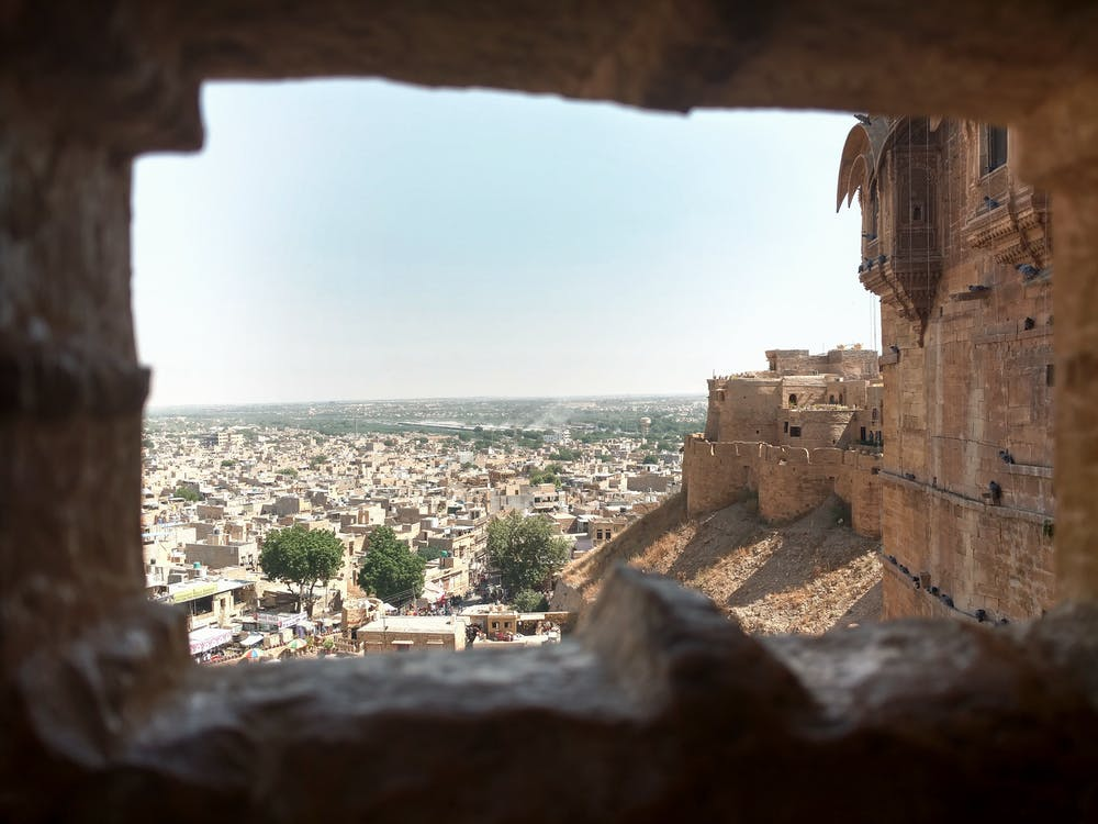 Distant ancient stone buildings of aged town with wall of medieval fort in India