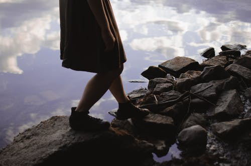 Unrecognizable woman walking on stony lake shore