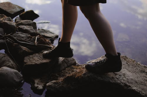 Woman in boots standing on stones near lake