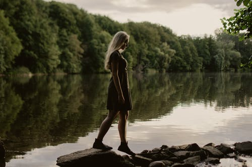 Young woman standing near lake in green forest