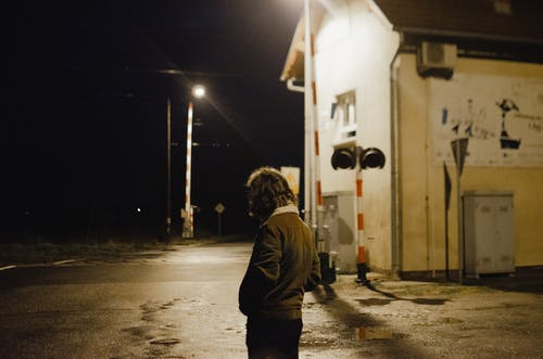 Side view of lonely unrecognizable male in warm jacket standing near illuminated railway crossing with shabby building and barriers at night time