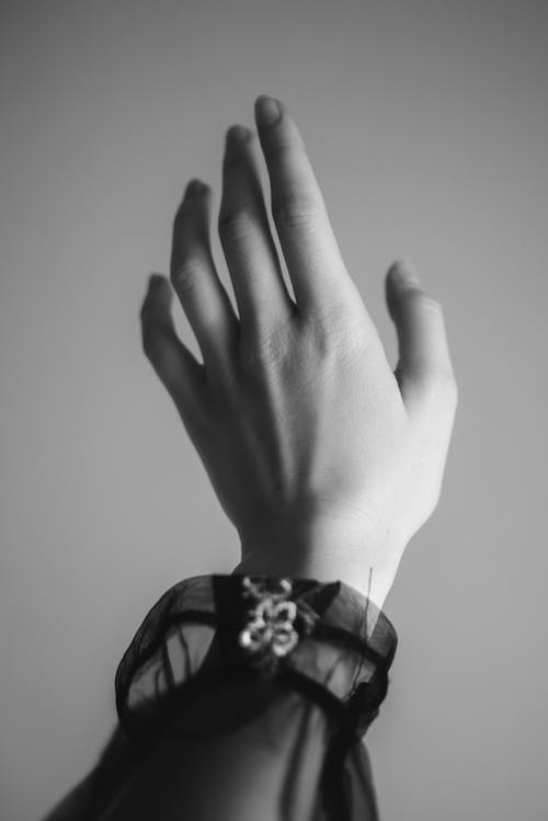 Black and white hand of crop anonymous young female wearing dark translucent clothes stretching up against wall