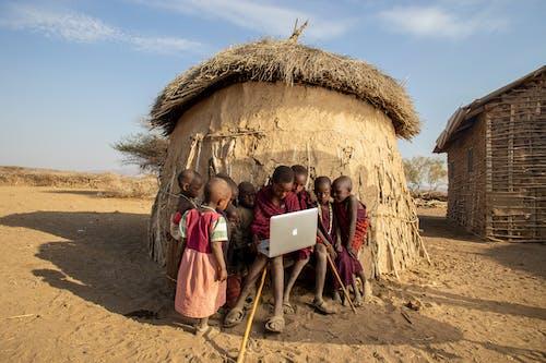 拿著白色便攜式計算機的桃紅色禮服的女孩