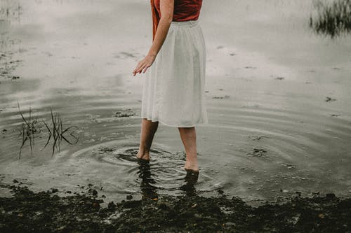 Side view of crop unrecognizable barefoot female in white skirt walking in water of pond in cloudy summer day