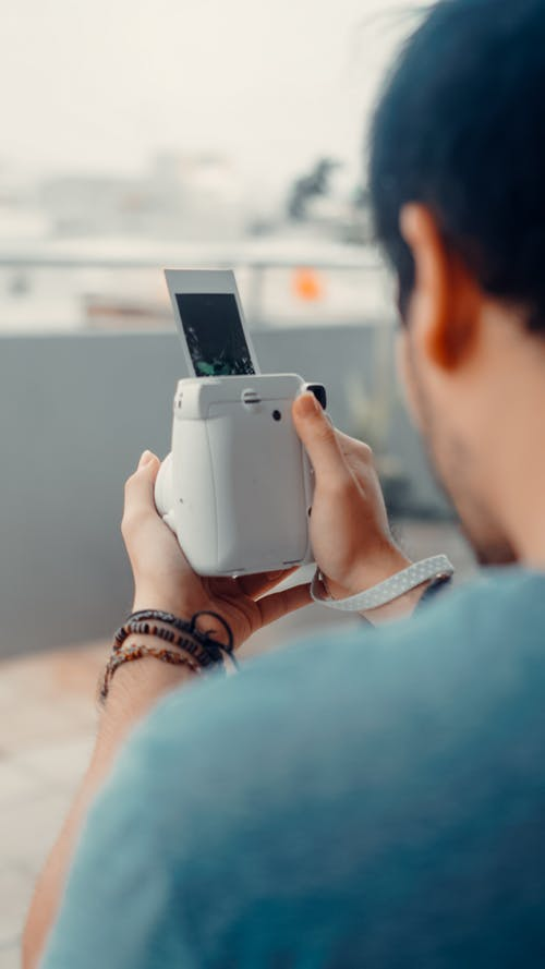 Man taking photo with instant camera