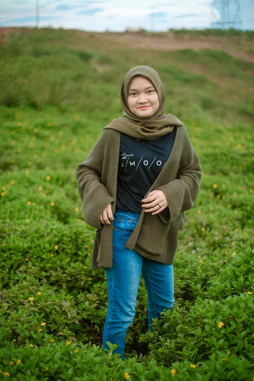 Smiling young ethnic woman standing in green field