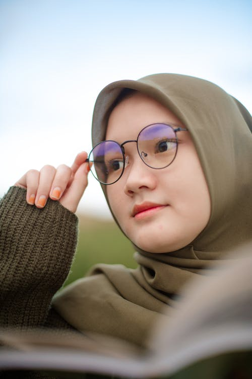 Low angle of modern Asian female teenager in traditional hijab and stylish eyeglasses standing against blurred field and sky
