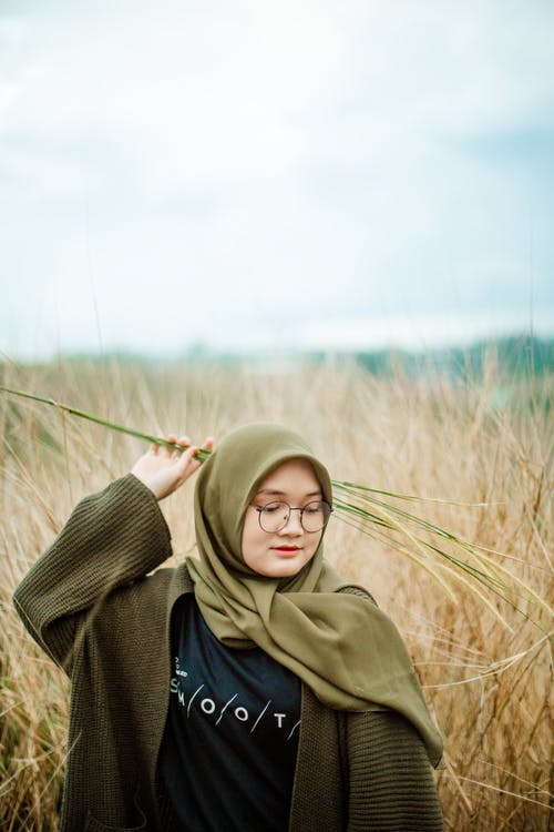 Young Asian teen female in eyeglasses wearing warm knitted clothes and headscarf holding green plant in hand while standing among tall dried grass in autumn field