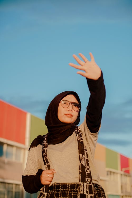 Low angle of modern young Asian female in black hijab and eyeglasses with bag over neck covering eyes from bright sun with outstretched arm while standing on urban street