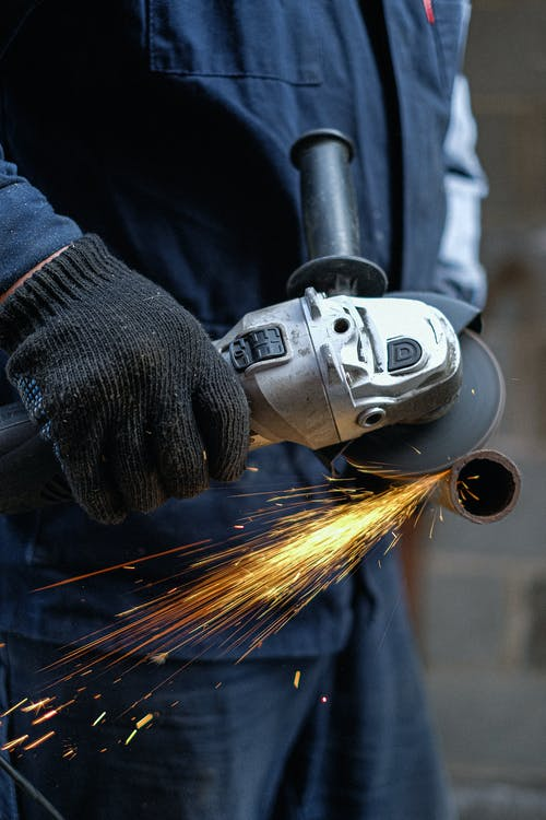 Person in Black Jacket Holding Gray and Black Power Tool