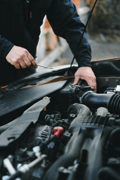 Person in Black Long Sleeve Shirt Holding Black Car Engine