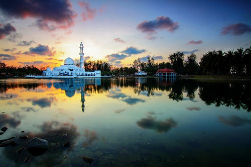 Picturesque sunset over lake with mosque on shore