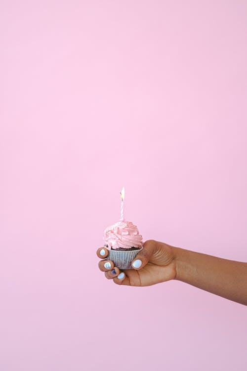 Person Holding Pink and White Cupcake With White Icing