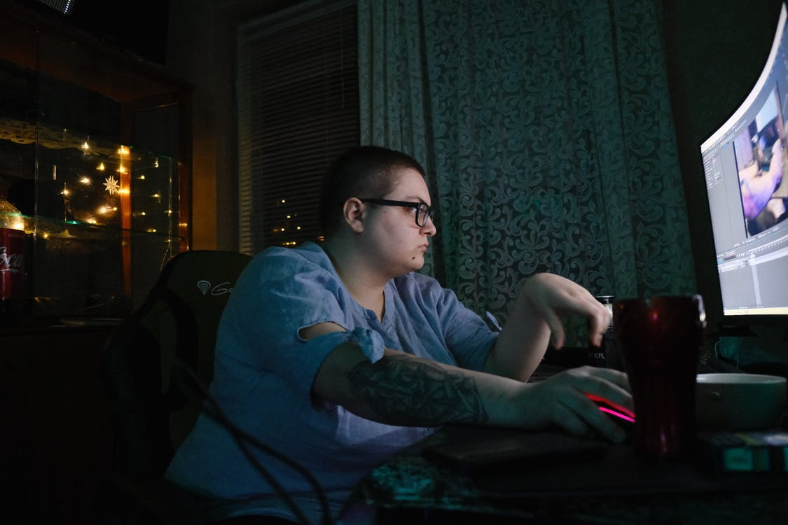 Side view of obese young male in eyeglasses with tattooed arm sitting at table and using computer with curved monitor while spending evening at home